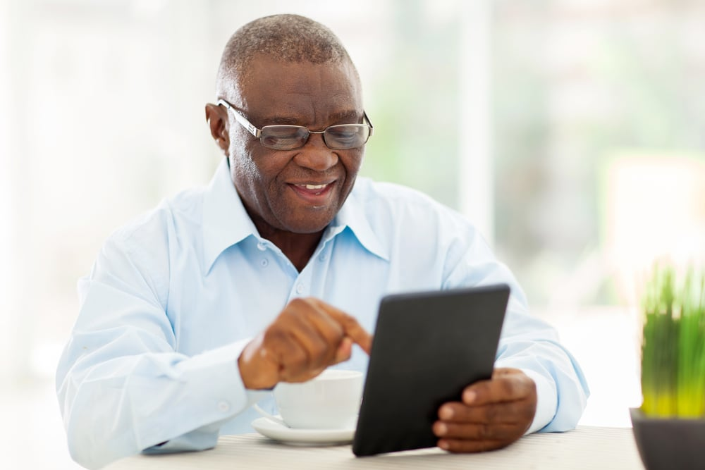 a smiling man holding an iPad and pointing at the screen