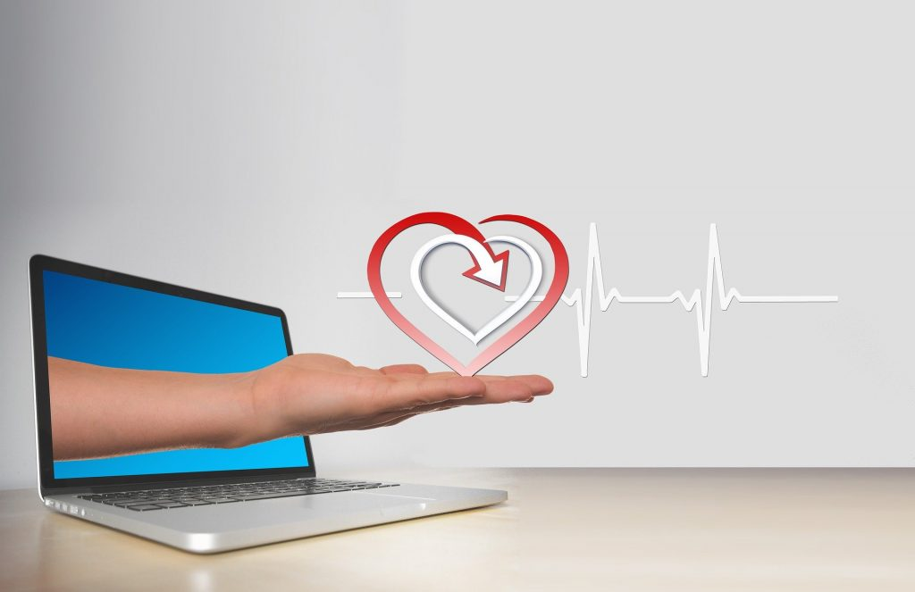 Hand reaching out from computer screen holding a heart with pulse