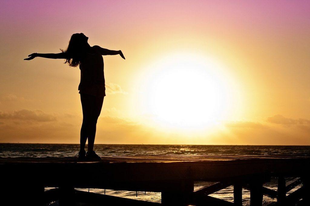 Happy woman at sunrise